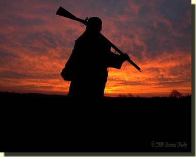 A traditional hunter backlit by a lavender sunrise.