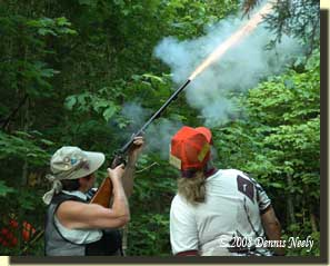 A double barrel shotgun belches fire in the woods